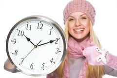 Fille dans le chapeau et l'écharpe d'hiver montrant l'horloge et les pouces  Photos stock