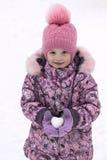 Fille dans le chapeau, le manteau et des mitaines tenant une boule de neige sous forme de coeur Image libre de droits