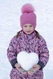 Fille dans le chapeau, le manteau et des mitaines tenant une boule de neige sous forme de coeur Images stock