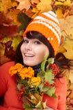 Fille dans le chapeau orange d'automne sur le groupe de lame, fleur. Photographie stock libre de droits