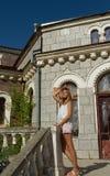 Fille dans le chapeau près de la vieille maison Image libre de droits