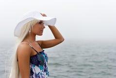 Fille dans le chapeau restant près de la mer brumeuse Image stock