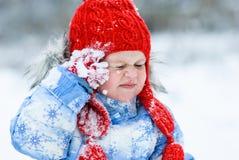 Fille dans le chapeau rouge marchant pendant l'hiver Photo stock