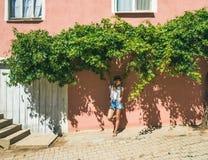 Fille dans le chapeau se tenant près du mur rose dans le village turc photos libres de droits