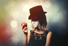 Fille dans le chapeau supérieur et masque blanc avec la pomme images stock