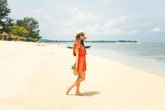 Fille dans le chapeau tenant l'ananas sur la plage Photo libre de droits