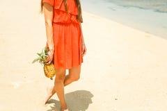 Fille dans le chapeau tenant l'ananas sur la plage Images libres de droits