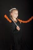 Fille dans le costume de Halloween avec la baguette magique magique sur le fond noir Images libres de droits