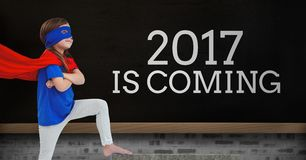 Fille dans le costume de super héros se tenant près d'un conseil avec 2017 citations de nouvelle année Images libres de droits