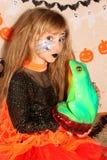 Fille dans le costume Halloween de sorcière embrassant une grenouille Images libres de droits