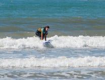 Fille dans le costume imperméable de couleur s'exerçant en surfant à bord Photo stock
