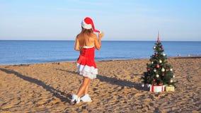Fille dans le costume sur la nouvelle station de vacances sur la plage avec les cadeaux 1 banque de vidéos