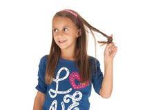 Fille dans le dessus bleu jouant avec ses cheveux Photos stock