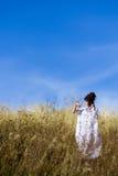 Fille dans le domaine avec le ciel bleu Photographie stock