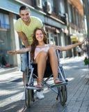 Fille dans le fauteuil roulant avec l'ami extérieur Photographie stock