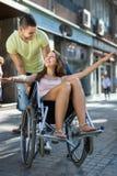 Fille dans le fauteuil roulant avec l'ami extérieur Photographie stock libre de droits