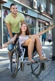 Fille dans le fauteuil roulant avec l'ami extérieur Photos stock