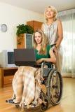 Fille dans le fauteuil roulant avec l'assistant féminin à la maison Photographie stock