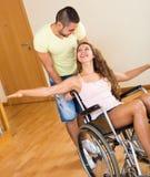 Fille dans le fauteuil roulant jouant avec l'ami Photos libres de droits