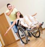 Fille dans le fauteuil roulant jouant avec l'ami Image stock