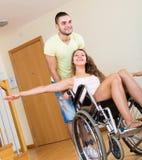 Fille dans le fauteuil roulant jouant avec l'ami Photo stock