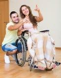 Fille dans le fauteuil roulant jouant avec l'ami Images stock