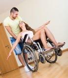 Fille dans le fauteuil roulant jouant avec l'ami Photos stock