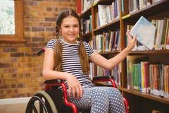 Fille dans le fauteuil roulant sélectionnant le livre dans la bibliothèque image libre de droits