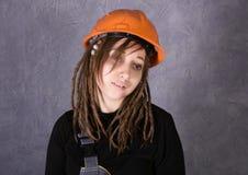 Fille dans le gilet orange de casque de sécurité tenant l'outil de marteau photos libres de droits