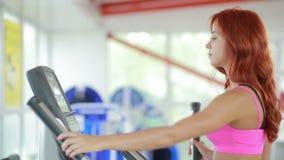 Fille dans le gymnase sur le simulateur La femme avec les jambes sportives marchant sur les steppers clips vidéos