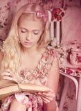 Fille dans le livre rose du relevé de robe Images stock