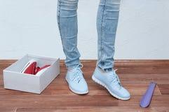 Fille dans le magasin essayant sur une paire d'espadrilles bleues Plan rapproché photographie stock libre de droits
