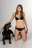 Fille dans le maillot de bain avec le dobermann sur le backgro blanc Photographie stock libre de droits