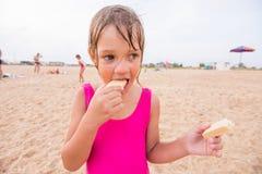 Fille dans le maillot de bain rose se tenant sur une plage sablonneuse Image stock