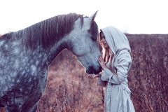 fille dans le manteau à capuchon avec le cheval, effet de la tonalité photos stock