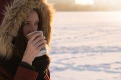 Fille dans le manteau chaud et le capot ayant une boisson chaude un jour froid Photographie stock