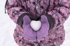 Fille dans le manteau et des mitaines tenant une boule de neige sous forme de coeur Images stock