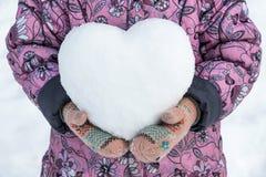 Fille dans le manteau et des mitaines tenant une boule de neige sous forme de coeur Photos stock