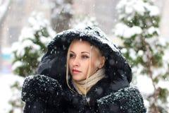 Fille dans le manteau noir sous la chute de neige - fermez-vous vers le haut du portrait Photo stock