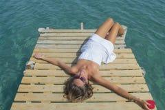 Fille dans le mensonge blanc sur le dock tenant un coeur dans sa main Photographie stock libre de droits