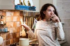 Fille dans le pijama d'hiver faisant cuire et buvant Image stock