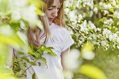 Fille dans le pommier de floraison Pommier fleurissant de ressort Une belle jeune femme dans un T-shirt blanc regarde vers le bas Photographie stock