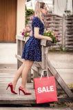 Fille dans le rétro support de robe sur un pont en bois, près d'un sac rouge Photos stock