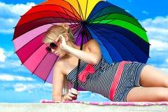 Fille dans le rétro type par le parapluie de couleur sur la plage Photos stock
