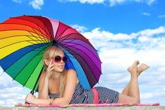 Fille dans le rétro type par le parapluie de couleur sur la plage Photographie stock libre de droits