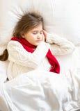 Fille dans le sommeil menteur de chandail et d'écharpe au lit Photographie stock libre de droits