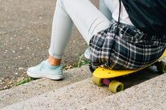 Fille dans le T-shirt blanc et des jeans se reposant sur le plastique jaune Image libre de droits