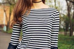 Fille dans le T-shirt rayé et avec les cheveux bruns en parc au printemps Images stock