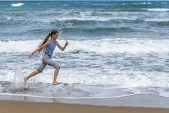 Fille dans le T-shirt rayé fonctionnant le long de la plage image libre de droits
