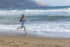 Fille dans le T-shirt rayé fonctionnant le long de la plage images stock